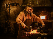 Senior blacksmith forging the molten metal on the anvil in smithy.  Stock Image