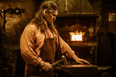 Senior blacksmith forging the molten metal on the anvil in smithy Stock Images