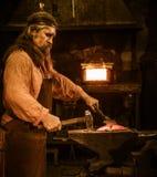 Senior blacksmith forging the molten metal on the anvil in smithy stock photography