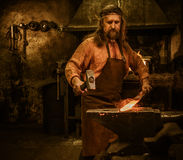 Senior blacksmith forging the molten metal on the anvil in smithy Royalty Free Stock Photography