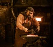 Senior blacksmith forging the molten metal on the anvil in smithy stock image