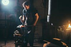 Senior blacksmith forging molten metal on the anvil in smithy. Stock Photography