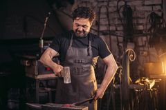 Senior blacksmith forging molten metal on the anvil in smithy. Royalty Free Stock Images