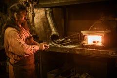 Senior blacksmith heats item before forgingin smithy stock images