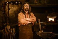 Senior blacksmith in smithy royalty free stock photos