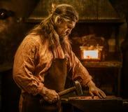 Senior blacksmith in smithy stock images