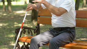 Senior blind man looking for his cane to stand up from bench and go for a walk. Stock footage stock footage