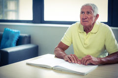 Senior blind man reading a braille book Stock Photography