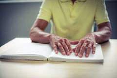 Senior blind man reading a braille book Royalty Free Stock Images