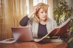 Something`s not right. Senior blonde business woman unhappy with the numbers she`s reviewing Stock Image