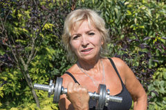 The senior blonde woman is holding a dumbbell Stock Photography
