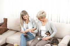 A senior blonde woman learns to use a tablet computer. She wants to learn how to buy cat food online. But she also wants to know