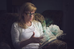Senior blonde woman reading a magic book Royalty Free Stock Photography