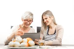 A senior blonde woman is sitting in the dining room with a young woman at the table. In front of them is a tablet computer, and a