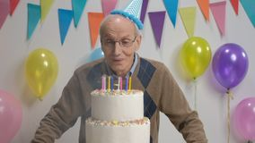 Senior blowing candles on a birthday cake and making a thumbs up gesture. Cheerful senior blowing candles on a birthday cake and making a thumbs up gesture stock video footage