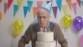 Senior blowing candles on a birthday cake stock video footage