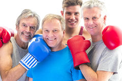 Senior boxing club with their trainer. Three senior men in gloves posing with their trainer Royalty Free Stock Photos