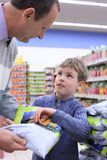 Senior with boy in shop Stock Photography