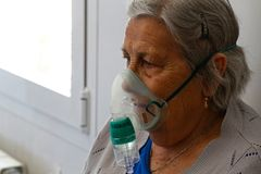 Senior wearing oxygen mask on a nursing home in Mallorca detail. A senior breathe an increased mix of oxygen in the infirmary of their nursing home in the royalty free stock photography