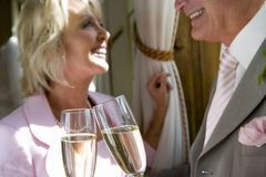 Senior bride and groom smiling at each other, toasting with champagne flutes, focus on glasses Stock Image