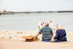 Senior British couple take a picnic by the sea, on Llandudno promenade. Llandudno, North Wales, United Kingdom. May 18 2014 : Senior British couple take a Stock Images