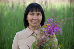 Senior brunette woman with willow-herb in field Royalty Free Stock Photo