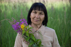 Senior brunette woman with willow-herb in field Stock Photos