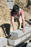 Senior builder. A senior builder putting up a new wall of a house, the second layer of bricks above the foundations Royalty Free Stock Photography