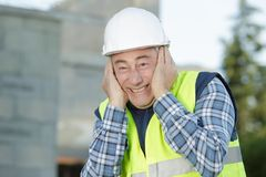 Senior builder covering ears in site. Senior builder covering his ears in site royalty free stock image