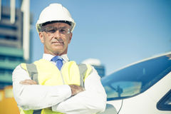 Senior builder man outdoors at construction site near his car lo Stock Photos