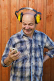 Senior builder in protective headphones holding hands in phone and reading message Royalty Free Stock Photos