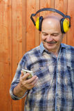 Senior builder in protective headphones holding hands in phone and reading message Stock Images