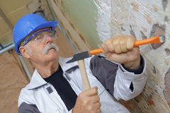 Senior builder using hammer and chisel. Builder royalty free stock photo