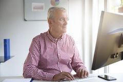 Senior buisnessman working in the office royalty free stock photography
