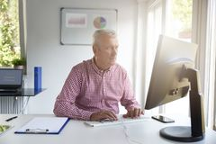 Senior buisnessman working in the office royalty free stock photos