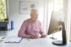Senior buisnessman working in the office royalty free stock images