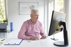 Senior buisnessman working in the office stock images