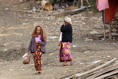 Senior Burmese woman walking in slum Stock Images
