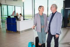 Senior Business Couple With Luggage In Airport Stock Image