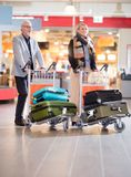 Senior Business Couple Walking With Luggage In Trolleys At Airpo Royalty Free Stock Photos