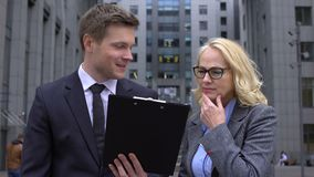 Senior business lady criticizing business project offered young male colleague stock footage