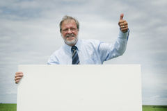 Senior business man. In a meadow with thumb up and a blank board Stock Photos
