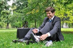 Senior business man changing shoes in park Royalty Free Stock Photography