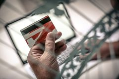 Business and finance. Senior business man checking his finance on credit card. Close up. Focus is on hand Stock Image