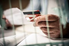 Credit card in hand. Senior business man checking his finance on credit card. Close up. Focus is on hand Royalty Free Stock Photo