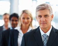 Senior business man with colleagues behind him Stock Image