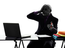 Senior business man computing displeased silhouette Stock Photo