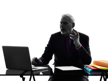 Senior business man computing displeased silhouette Royalty Free Stock Photography
