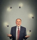 Senior business man executive in suit juggling playing with light bulbs. Portrait happy senior business man executive in suit juggling playing with light bulbs Stock Images