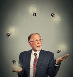 Senior business man executive in suit juggling playing with light bulbs. Portrait happy senior business man executive in suit juggling playing with light bulbs Stock Image